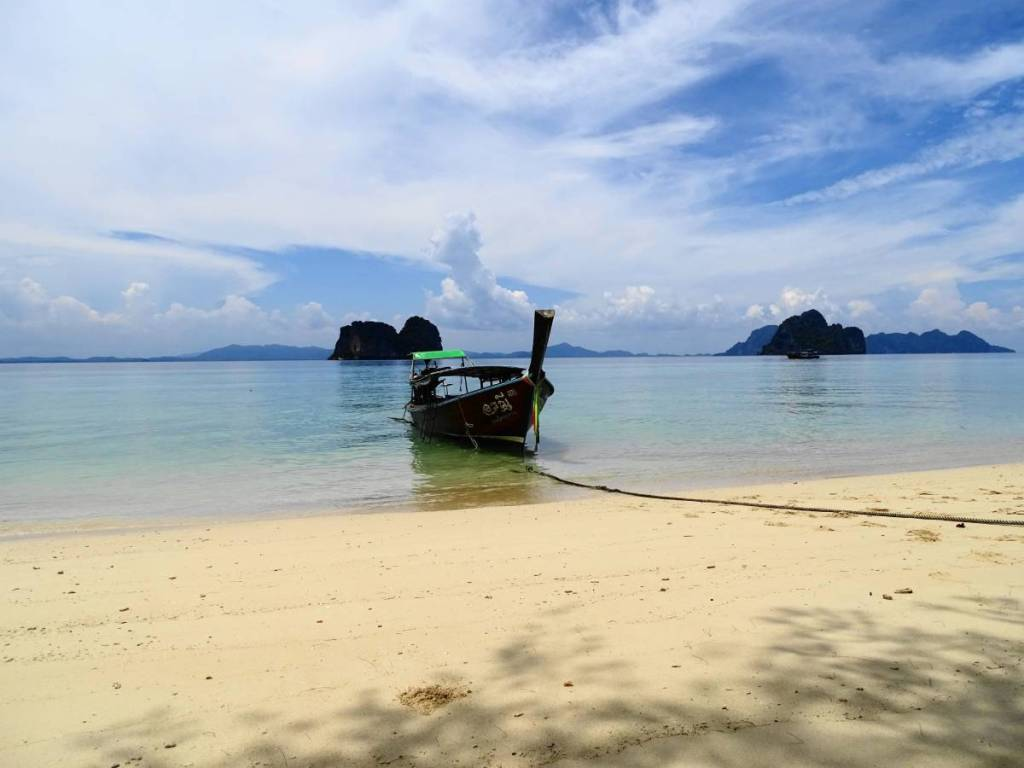 A long tail boat moored at the white sand beach on an island in southern Thailand. Karst rocks rise from the  turquoise see in the background.