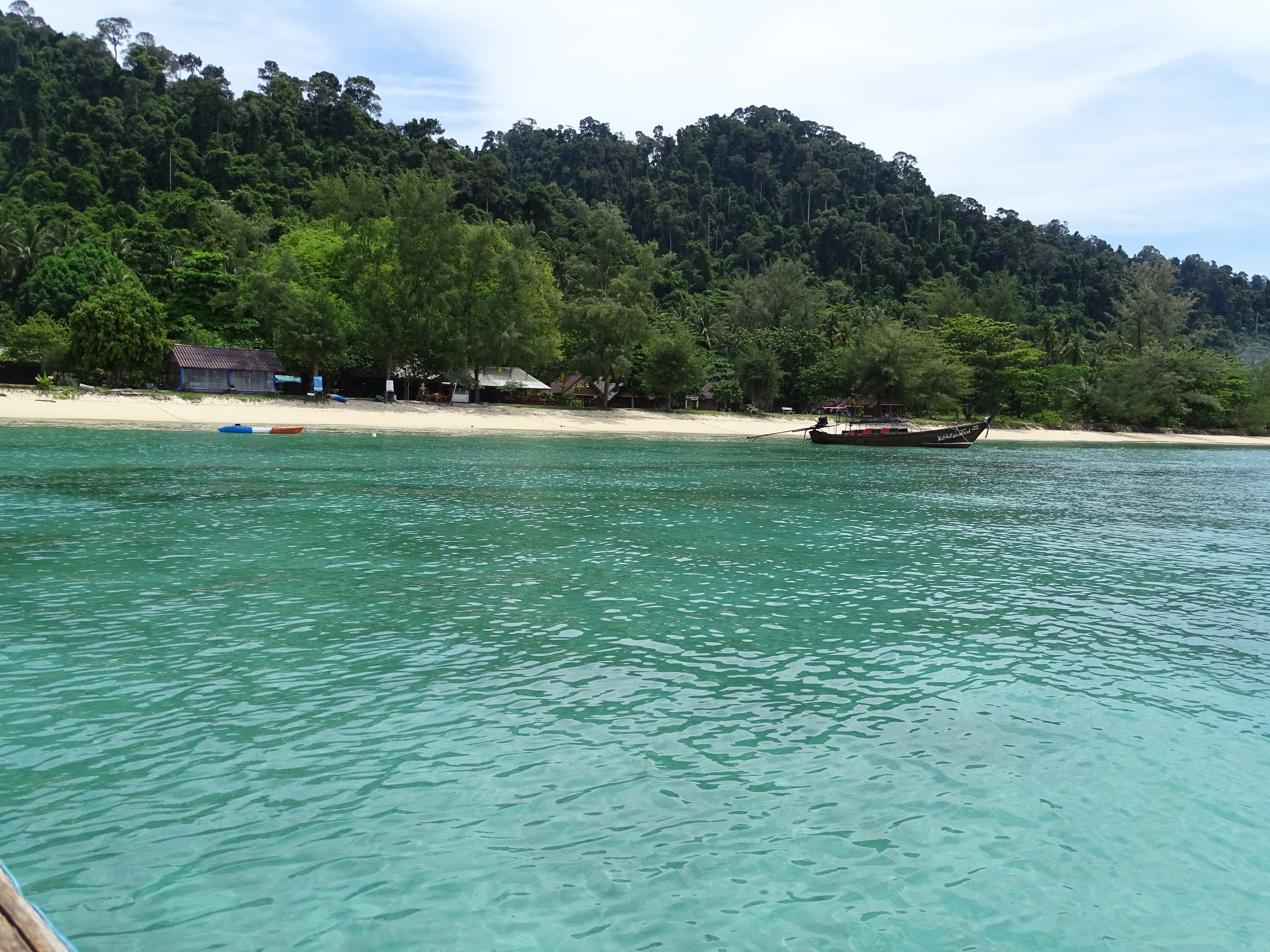 few huts, white beach and trees in Koh Ngai island from the sea