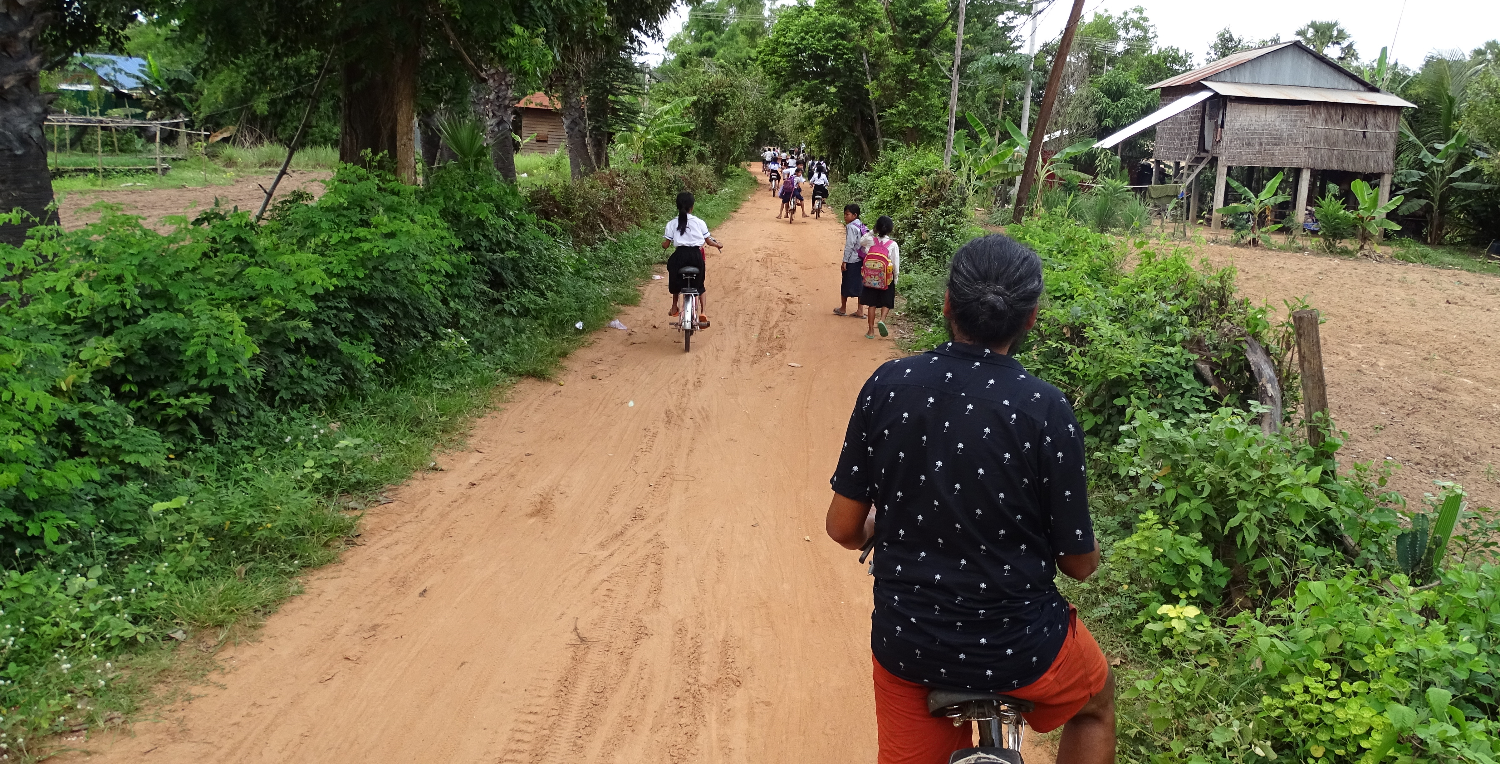 Sayak cycling on a dirt road in a Cambodian village, among children ins school uniforms