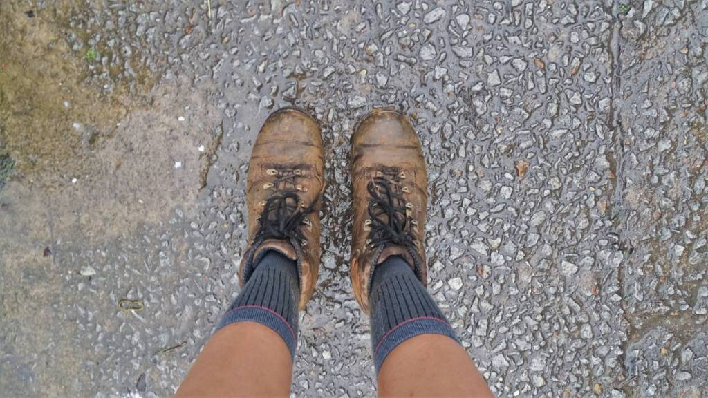 A selfie of legs and wet and muddy hiking boots after a hike in Vietnam