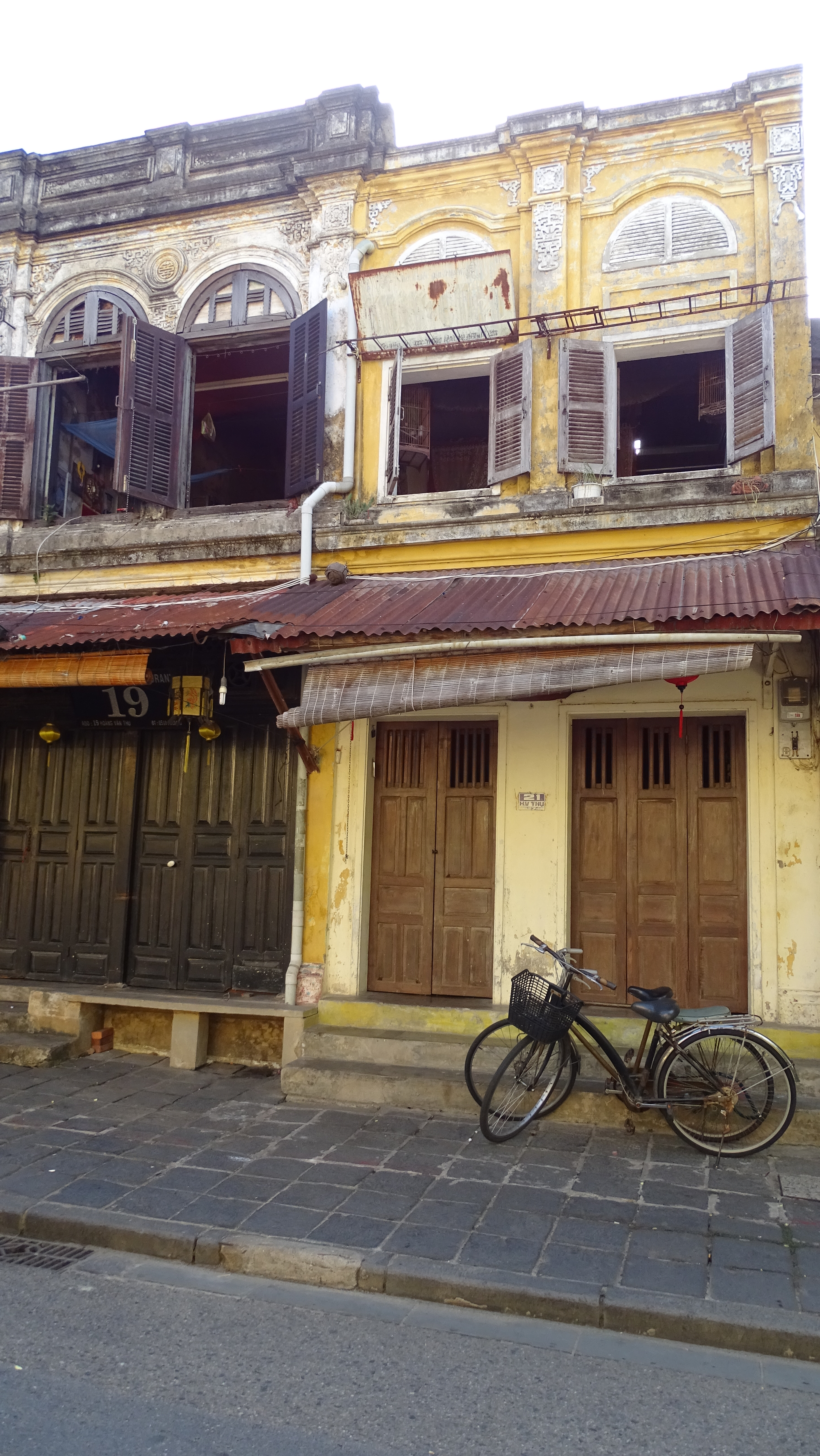 Two bicycles parked in front of the wooden doors of a yellow, historical house in Hoi An old town