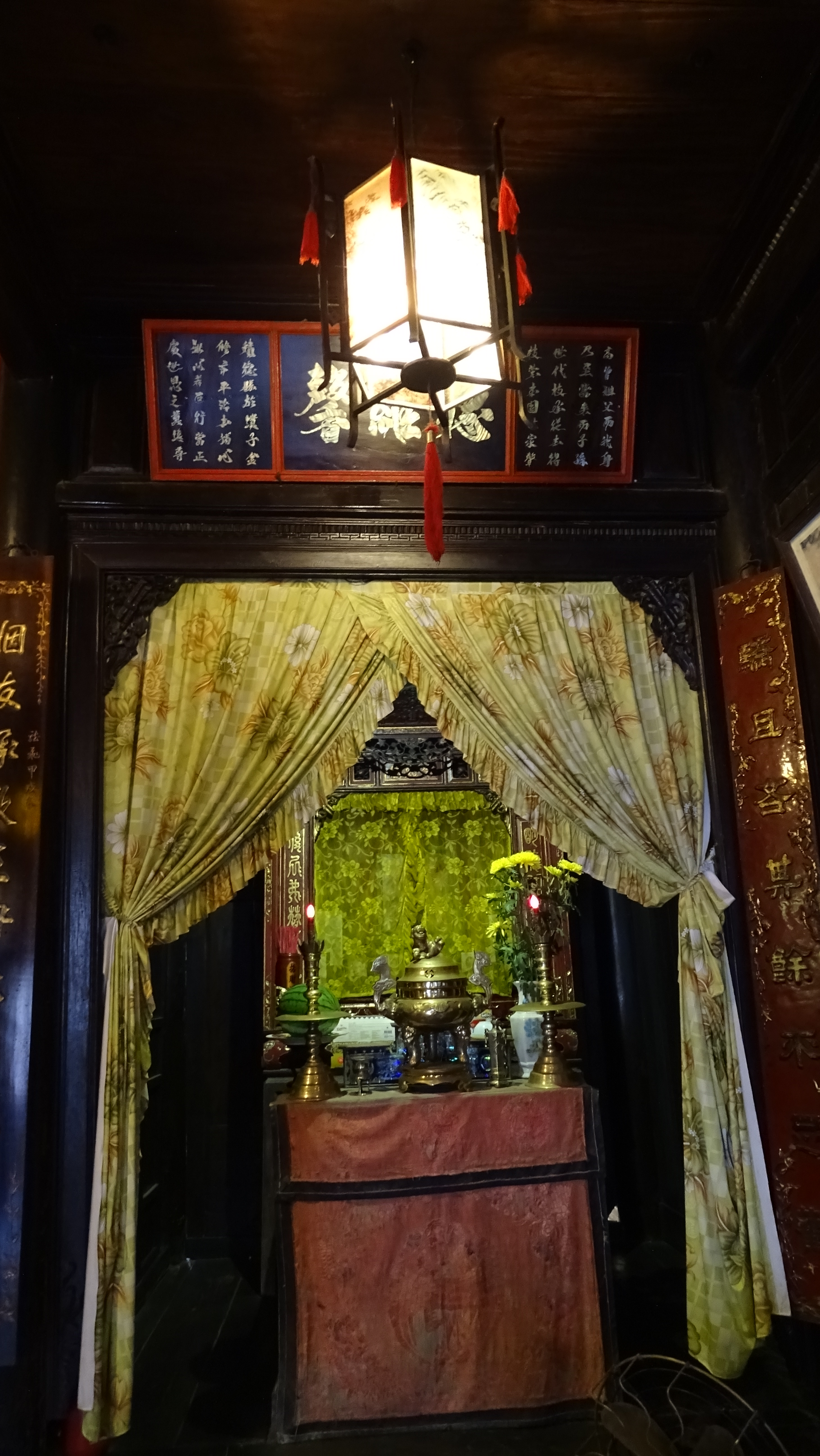 A paper lantern hanging above a home altar hidden behind the curtains in a wooden cabinet decorated with Chinese characters