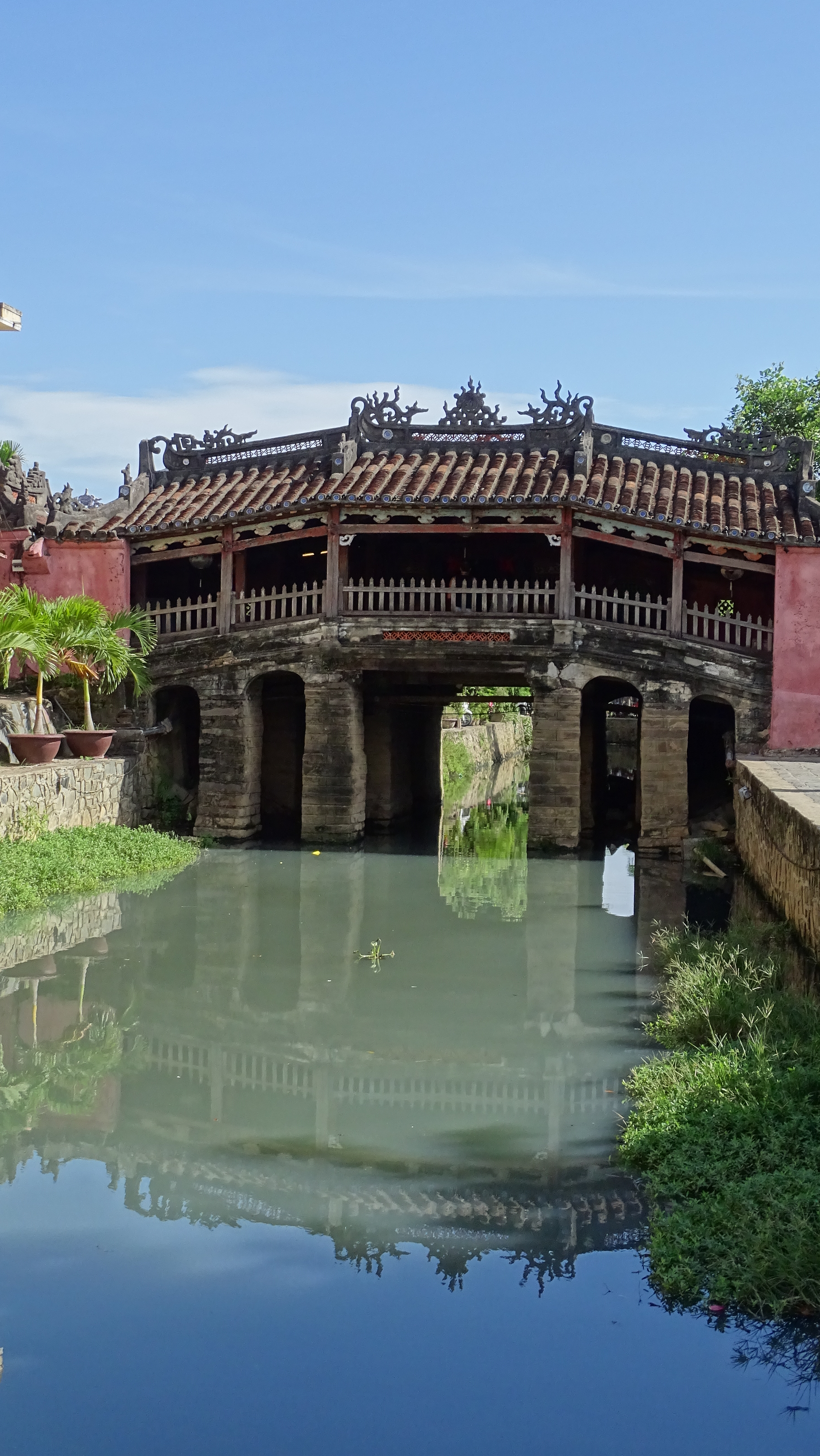 Covered stone Japanese Bridge reflecting in the canal below it