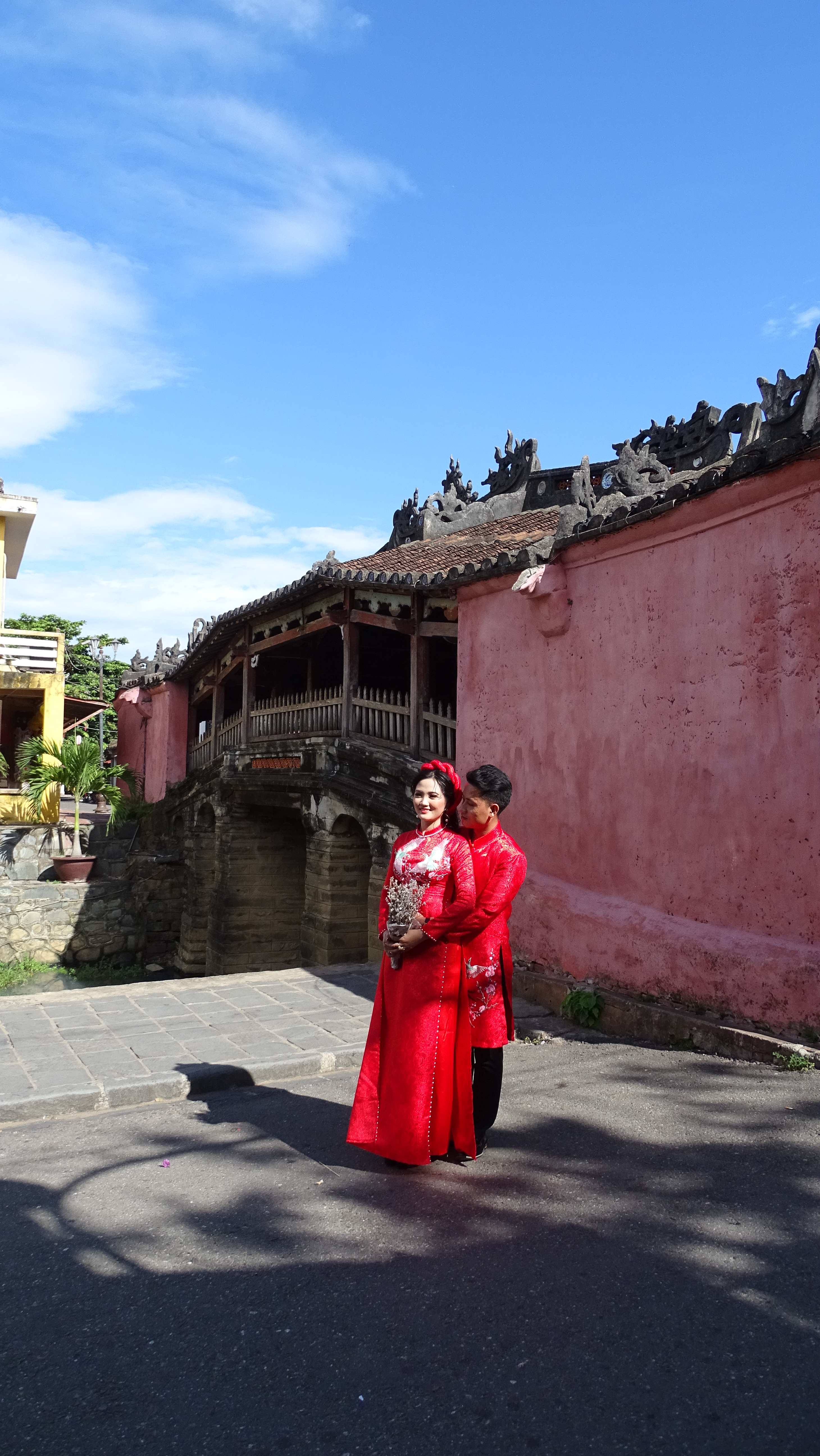 Vietnamese couple dressed in traditional, red costumes poses for their wedding photo in front of the covered Japanese Bridge