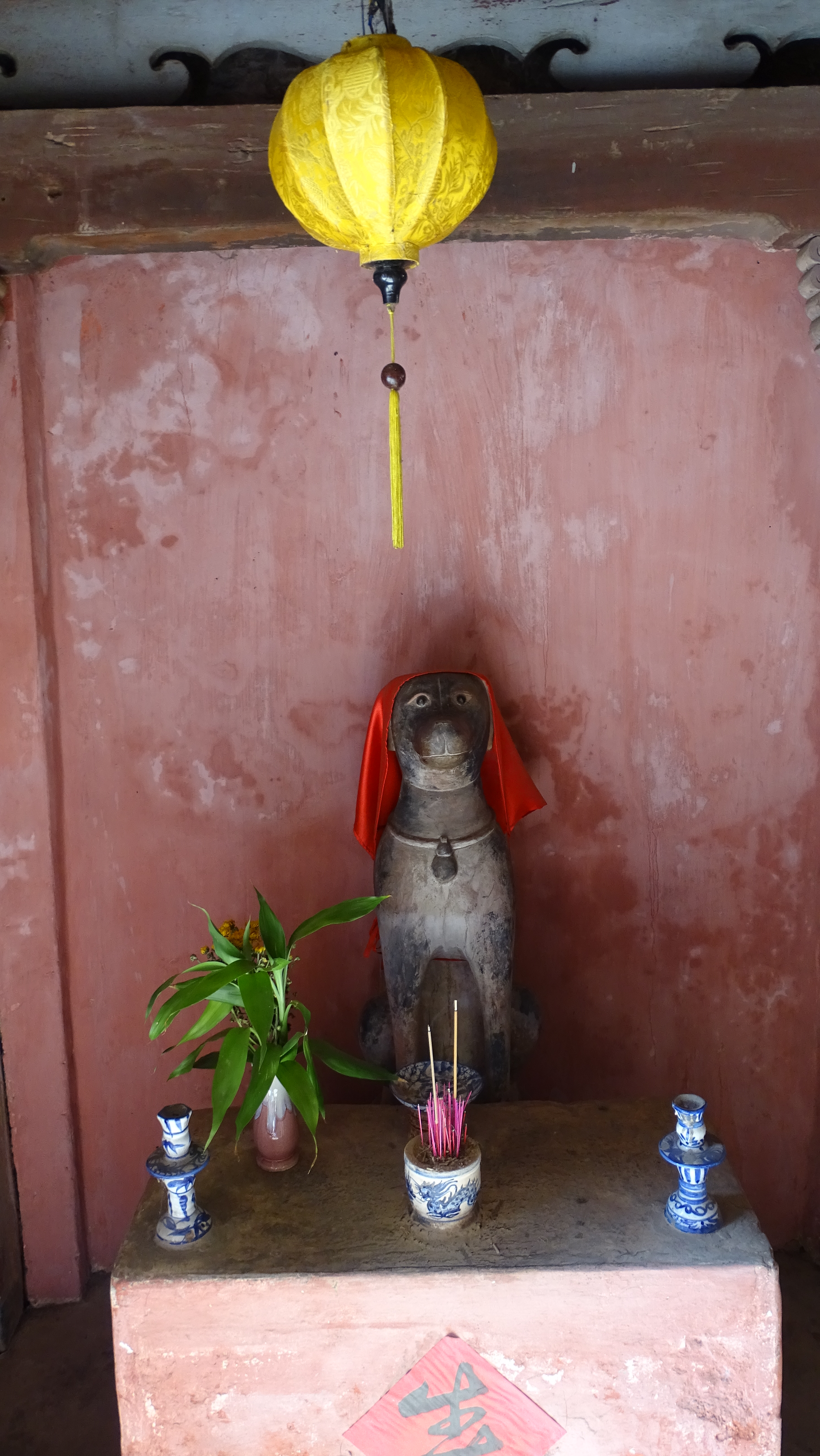 An altar with a statue of a dog draped in a red cloth with a yellow paper lantern hanging above it