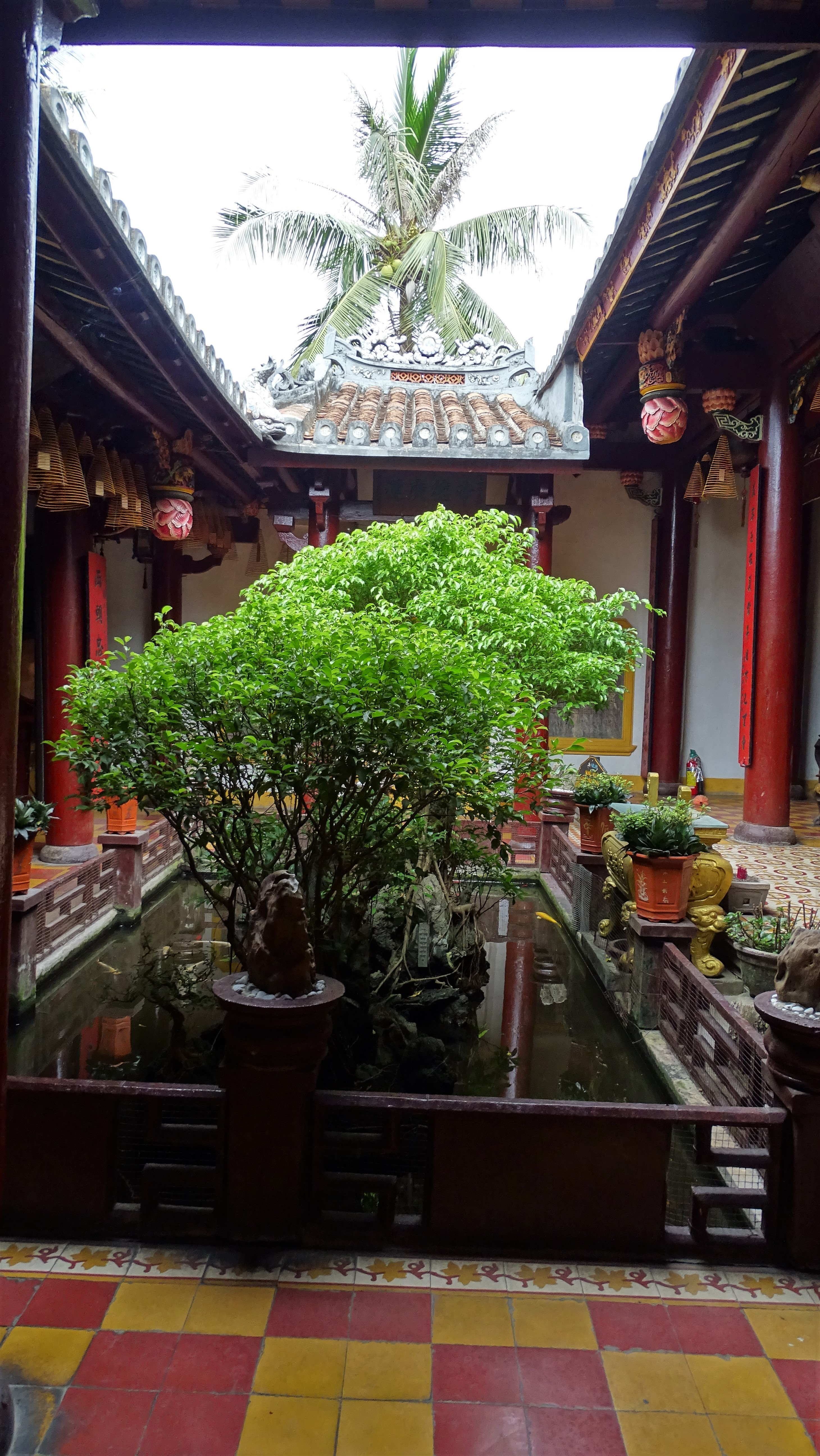 Quong Cong temple inner courtyard  lined with red columns and featuring a pond with plants in pots