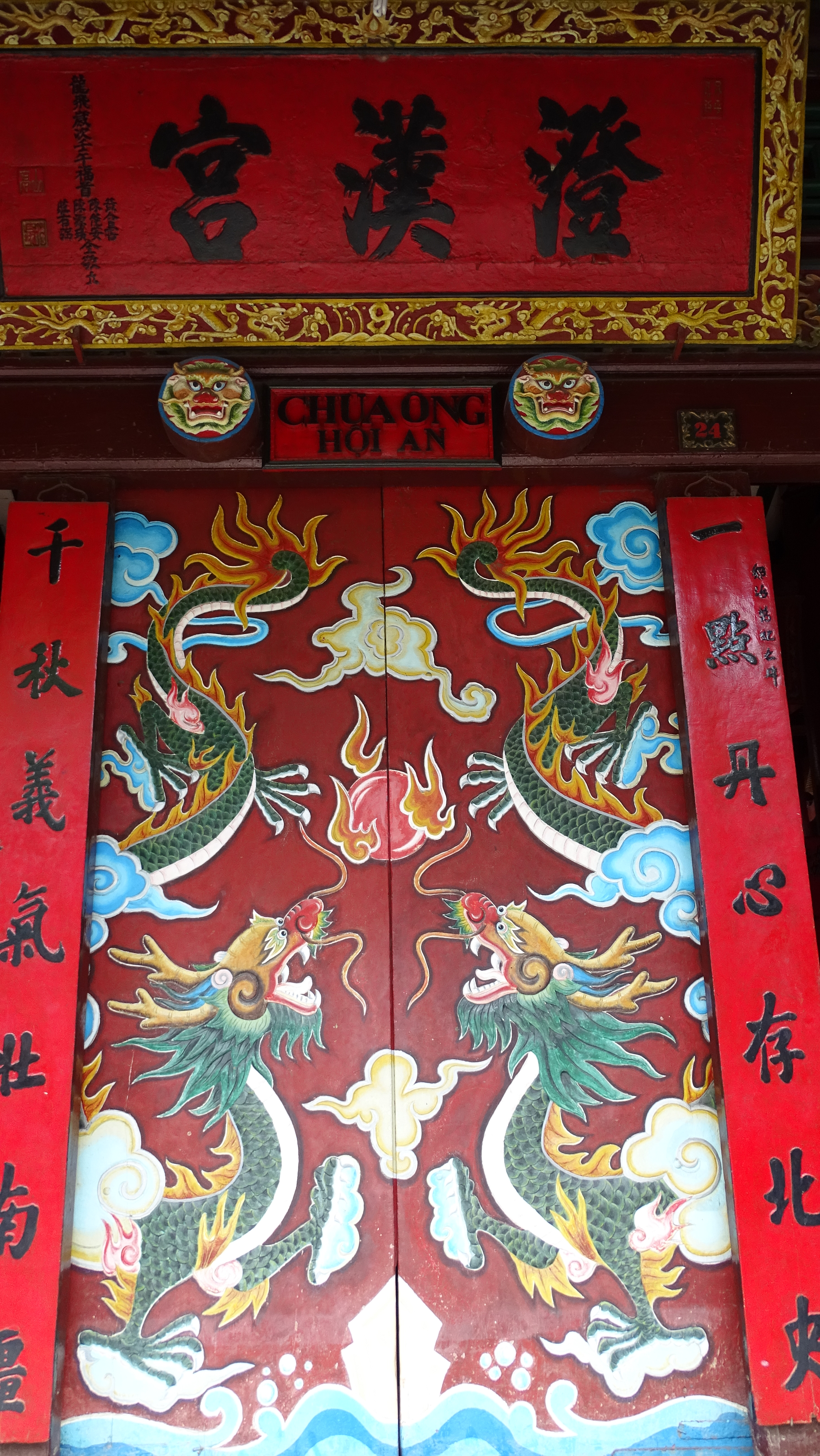 Red wooden doors to Chua Ong temple in Hoi An, decorated with dragons