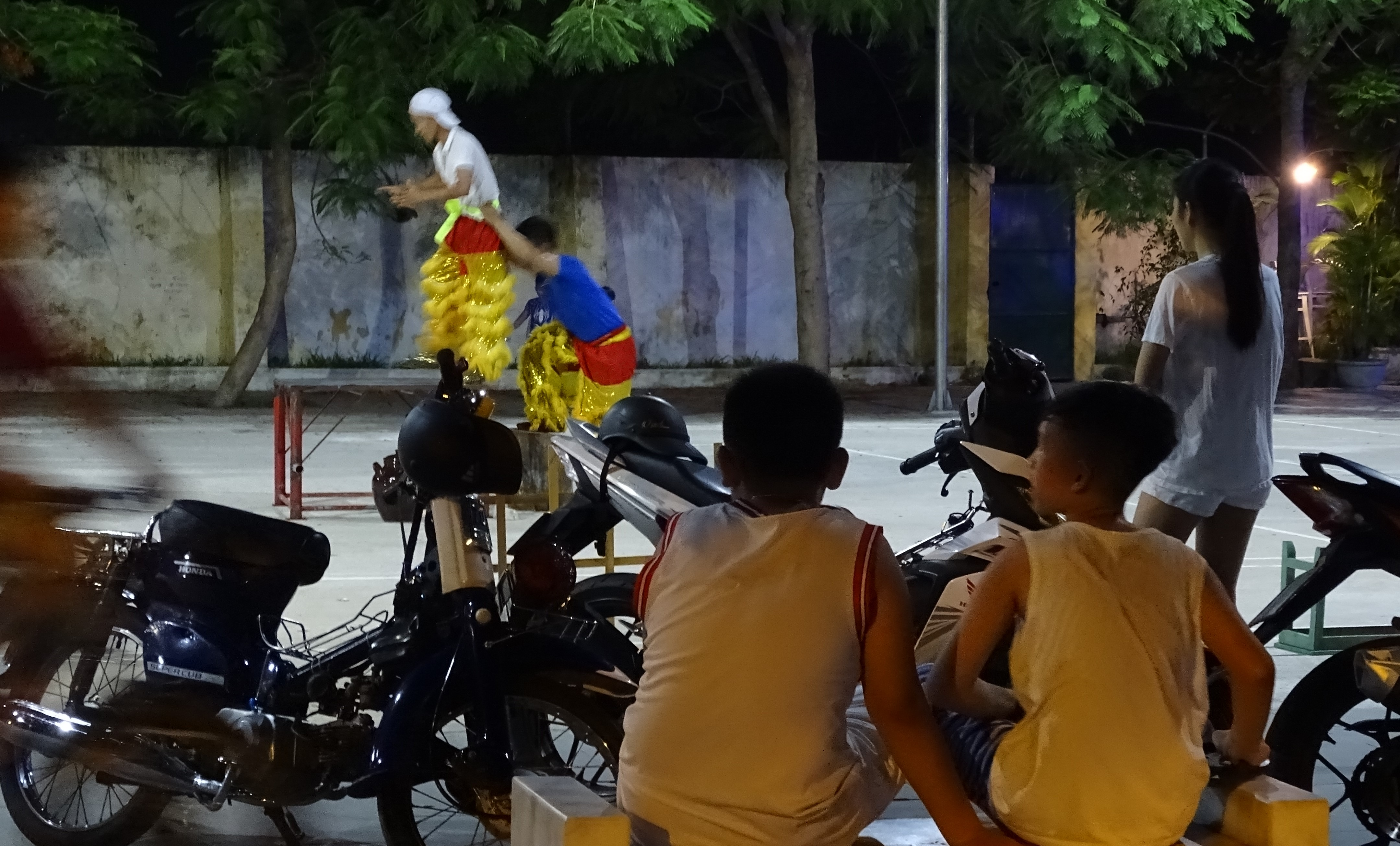Kids watching two young man wearing golden trousers and rehearsing the moves of the dragon dance