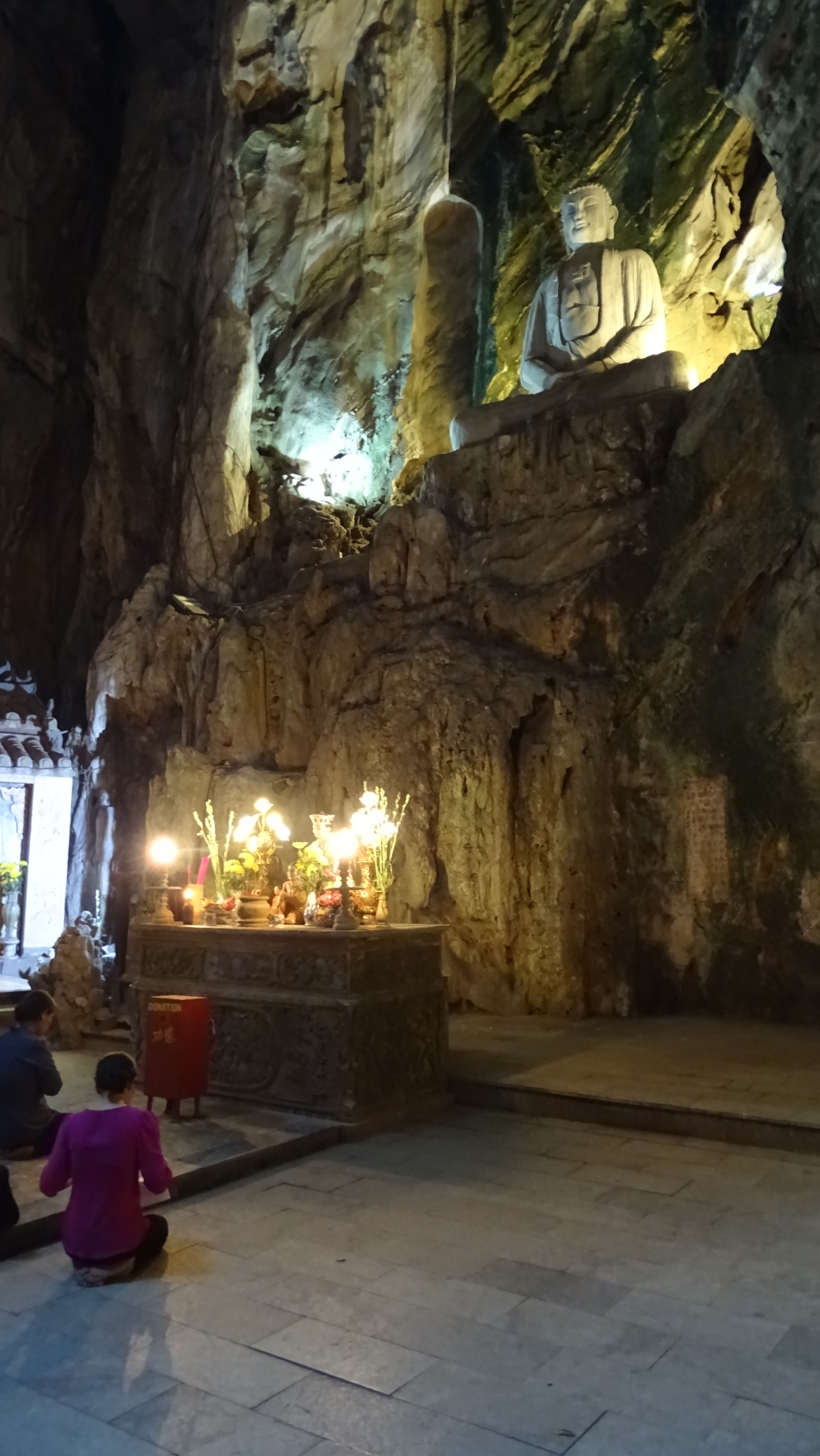 Buddhist devotees praying in front of an altar inside Hueyn Khong Cave in the Marble Mountains