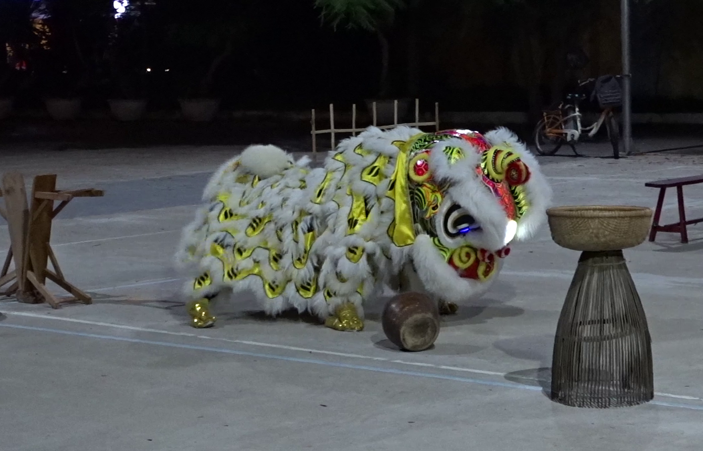 Part of a dragon dance: a short white-golden dragon playing with a jar.