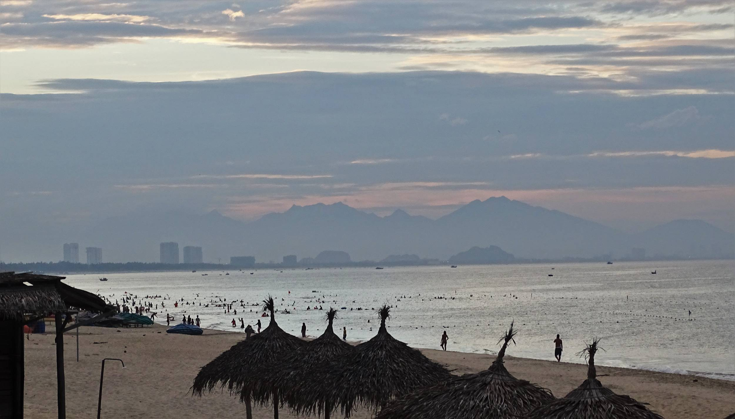 The view from An Bang beach at the sea, Da Nang city and the mountains on the horizon