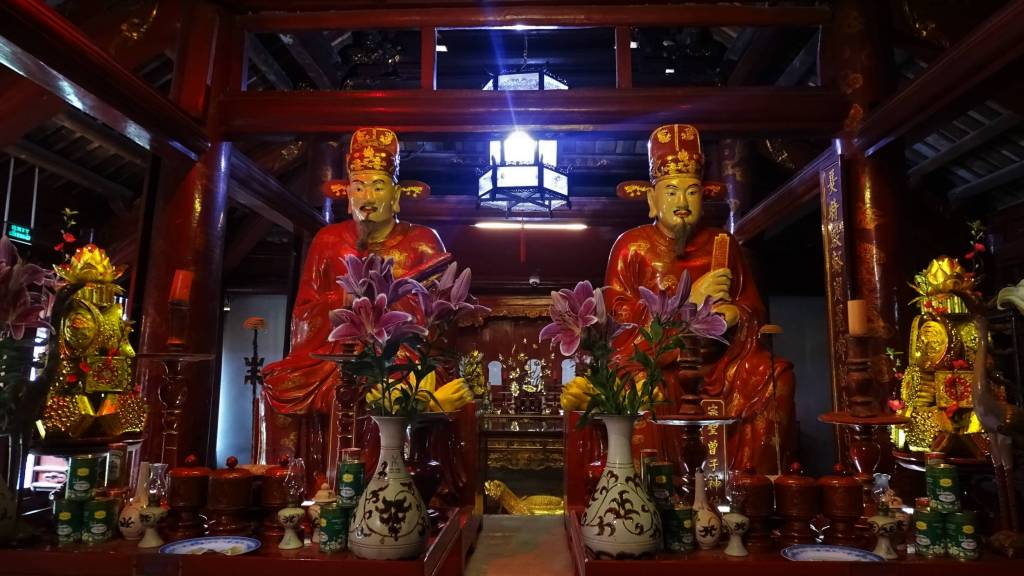 Two identical statues of oriental male dressed in red robes at the altar at the Temple of Literature in Hanoi