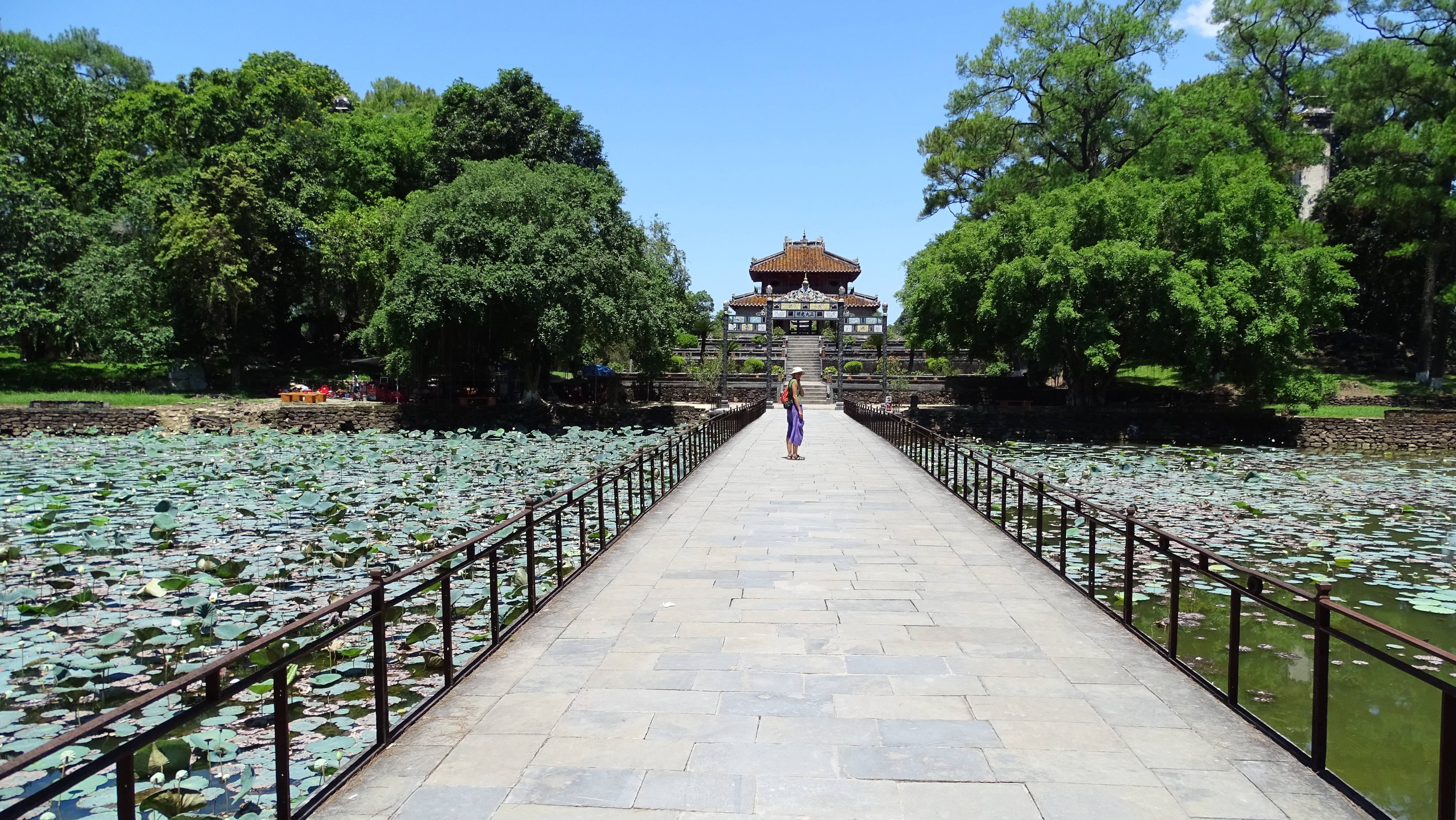 The author standing on the bridge over a a pond full of lotus flowers, leading to one of many pagodas at Minh Manh tomb
