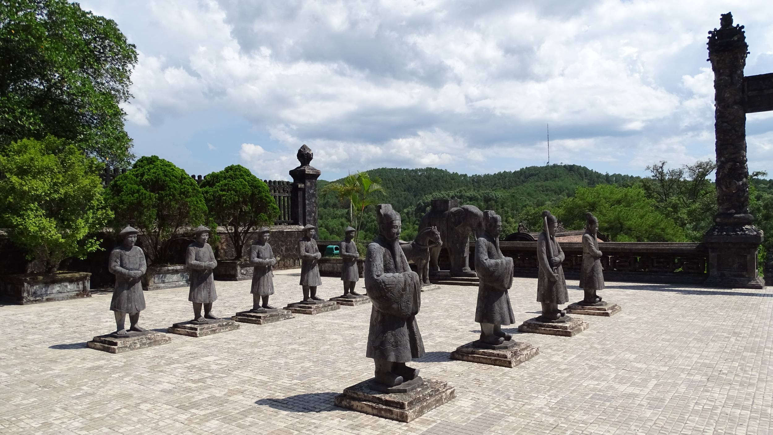 Two rows of concrete statues of mandarins and their servants standing at the platform at Kai Dinh tomb