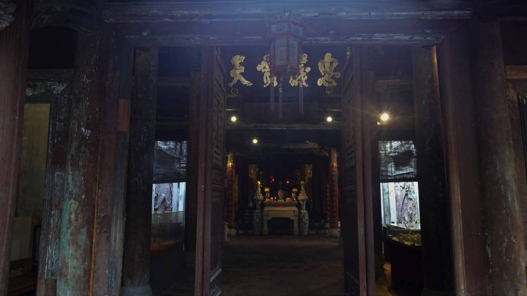 Open wooden doors showing the dark interior of a small temple. Hanoi Old Quarter
