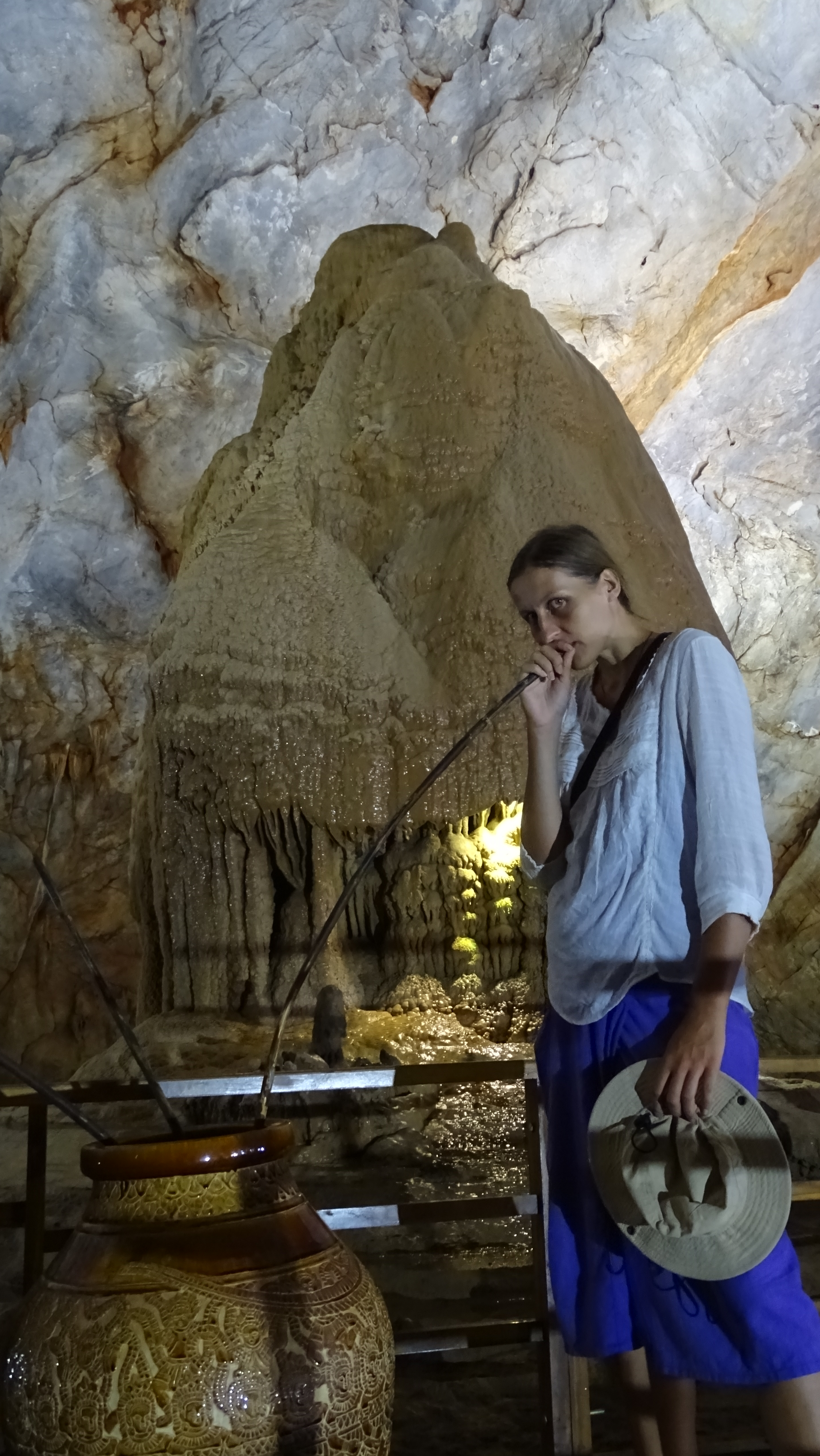 The author pretending to drink  wine from a jar placed in front of a rock formation resembling traditional rong hut inside the Paradise Cave