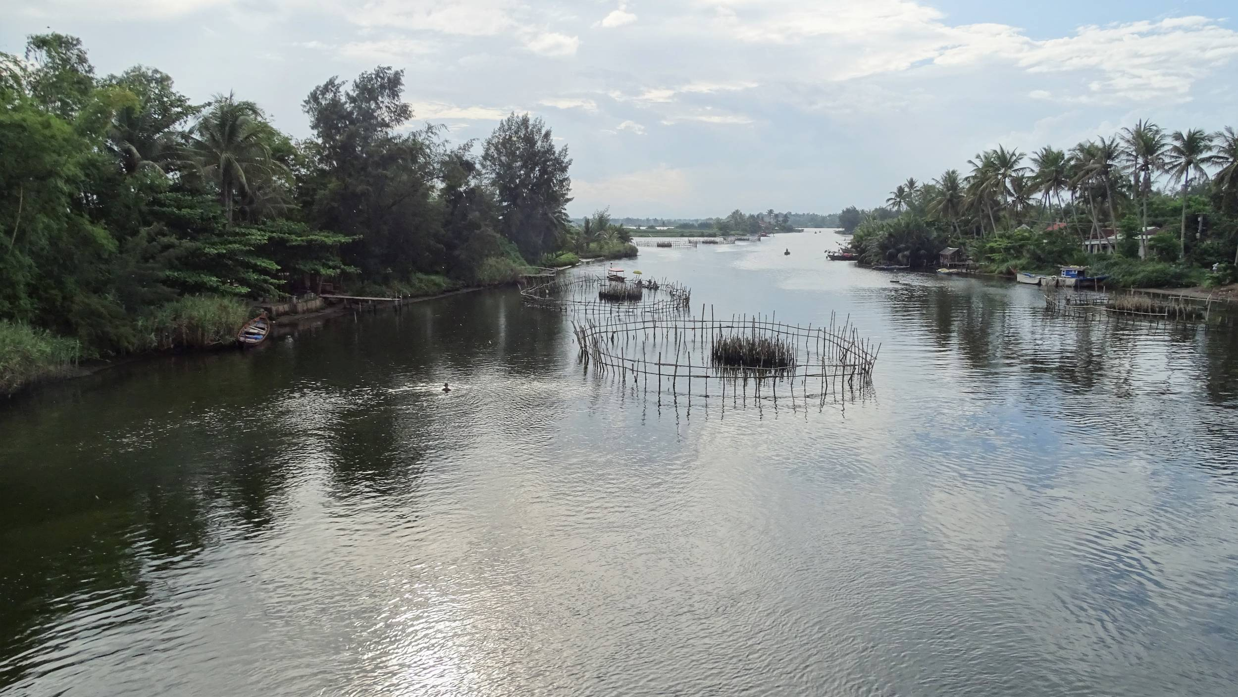 A large circular fishing trap in the middle of a small river