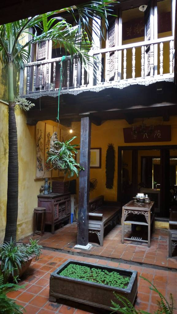 A little patio inside a heritage house in Hanoi Old Quarters, featuring wooden balcony , pots with plants and a seating area downstairs