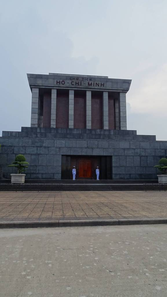 Two guards in white uniforms standing in front of monumental, gray cube of the Ho Chi Minh Mausoleum