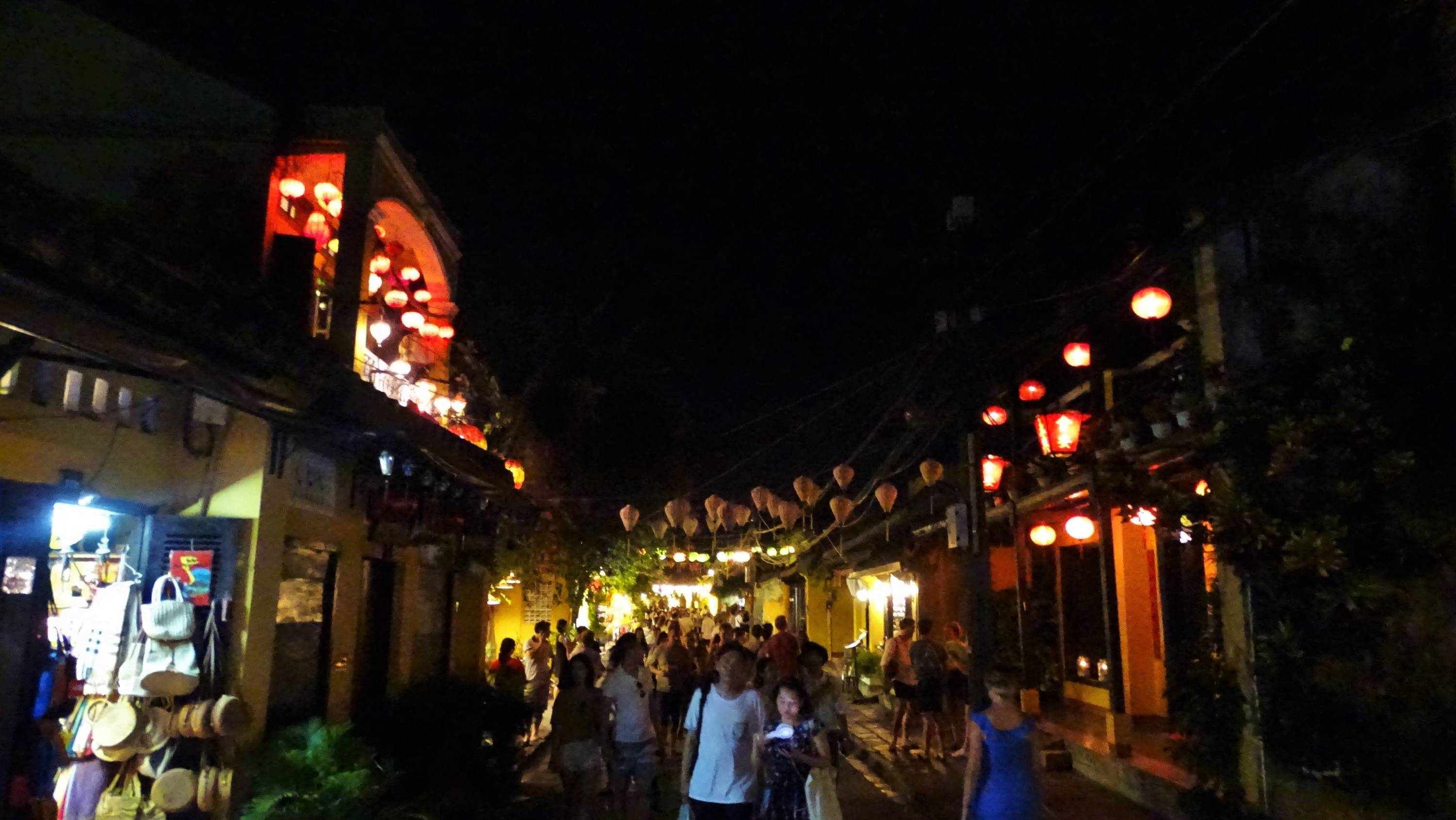 Crowds walking under lit paper lanterns in Hoi An old town