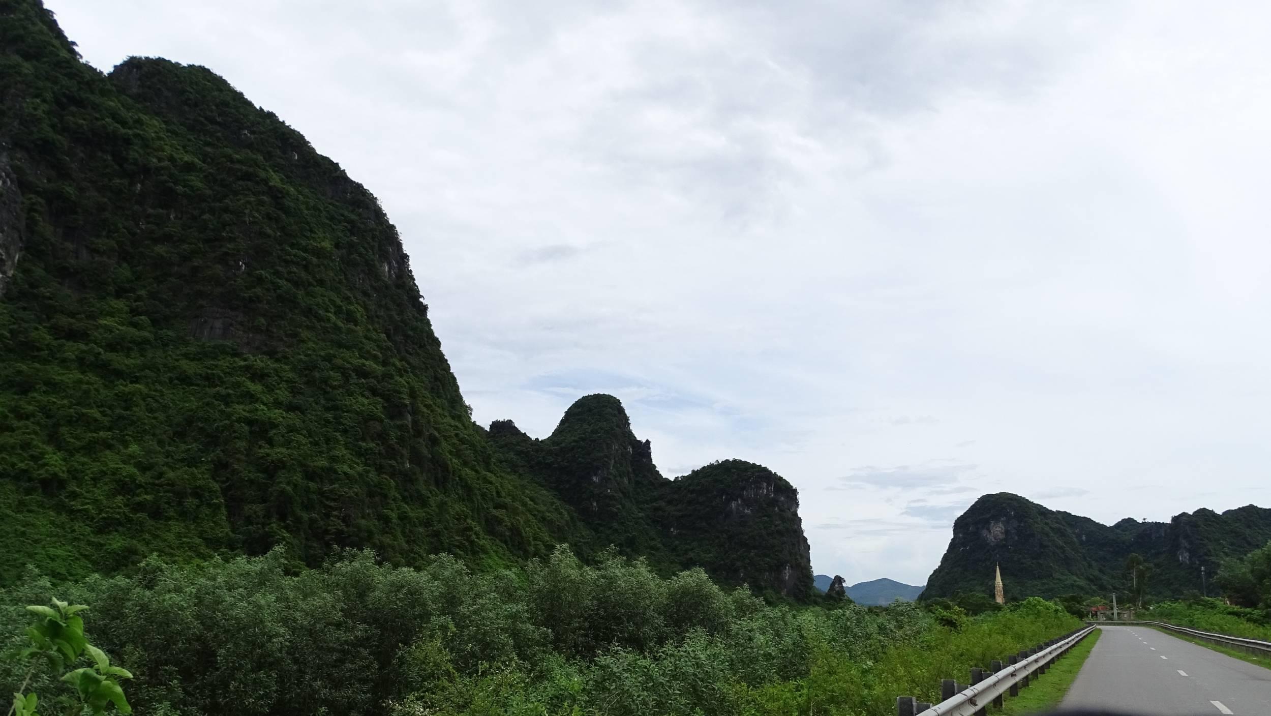 Karst rocks covered with greenery seen from the road to Phong Nha Ke Bang National Park