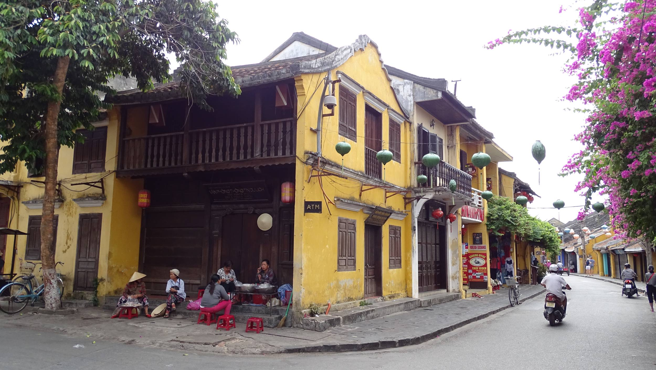 The local women sit on the red low stools in front of a yellow, historical building in  Hoi An  old town