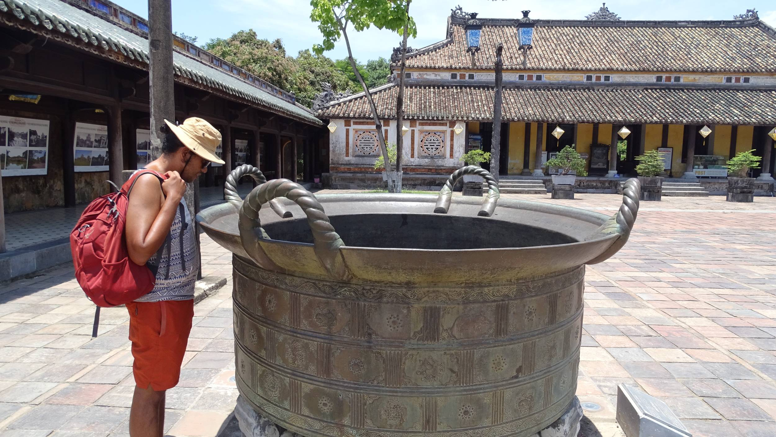 Sayak looking inside a huge bronze cauldron on one of the courtyards of the Imperial City in Hue