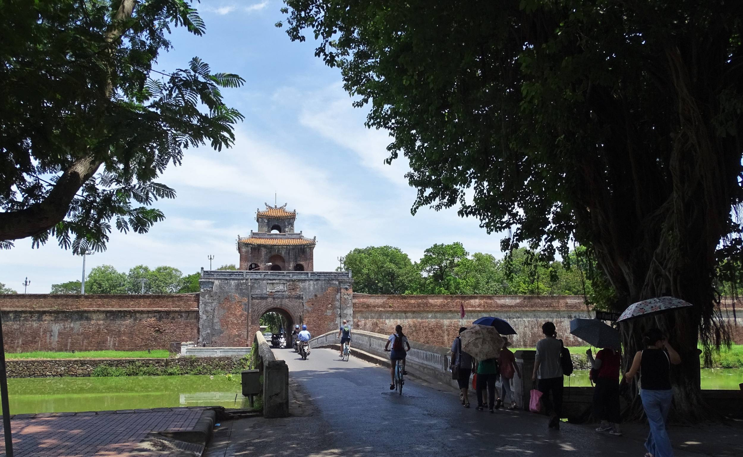 Pedestrians and two-wheel drivers crossing the bridge over the moat leading to the Hue Citadel