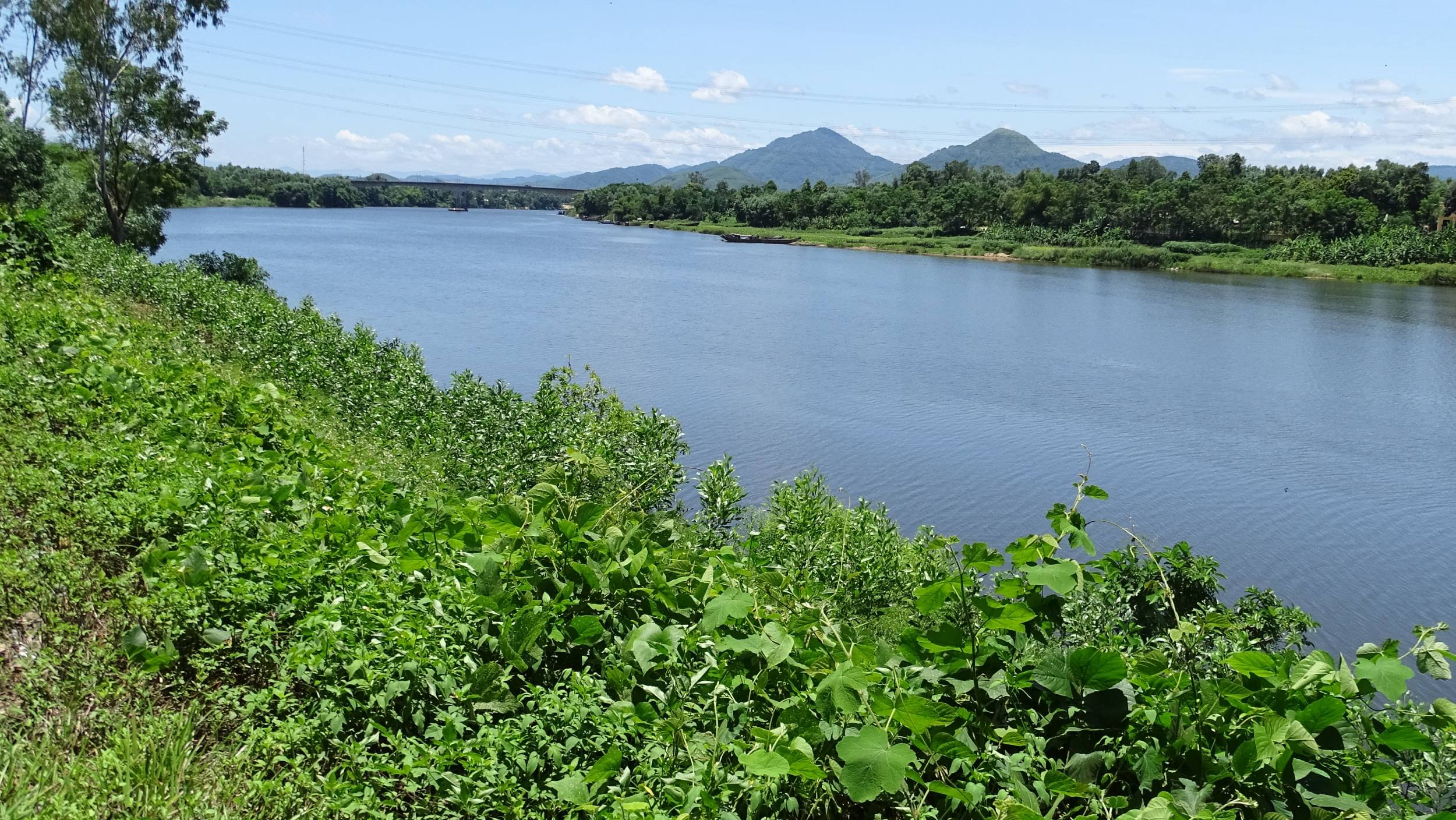 A view at the green banks of the Perfume River and the mountains in the distance from the road to Minh Manh tomb