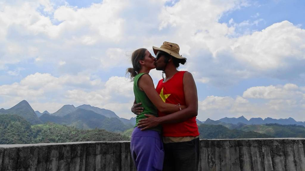 Kissing on the tower overlooking the mountain landscape in Dong Van, Vietnam