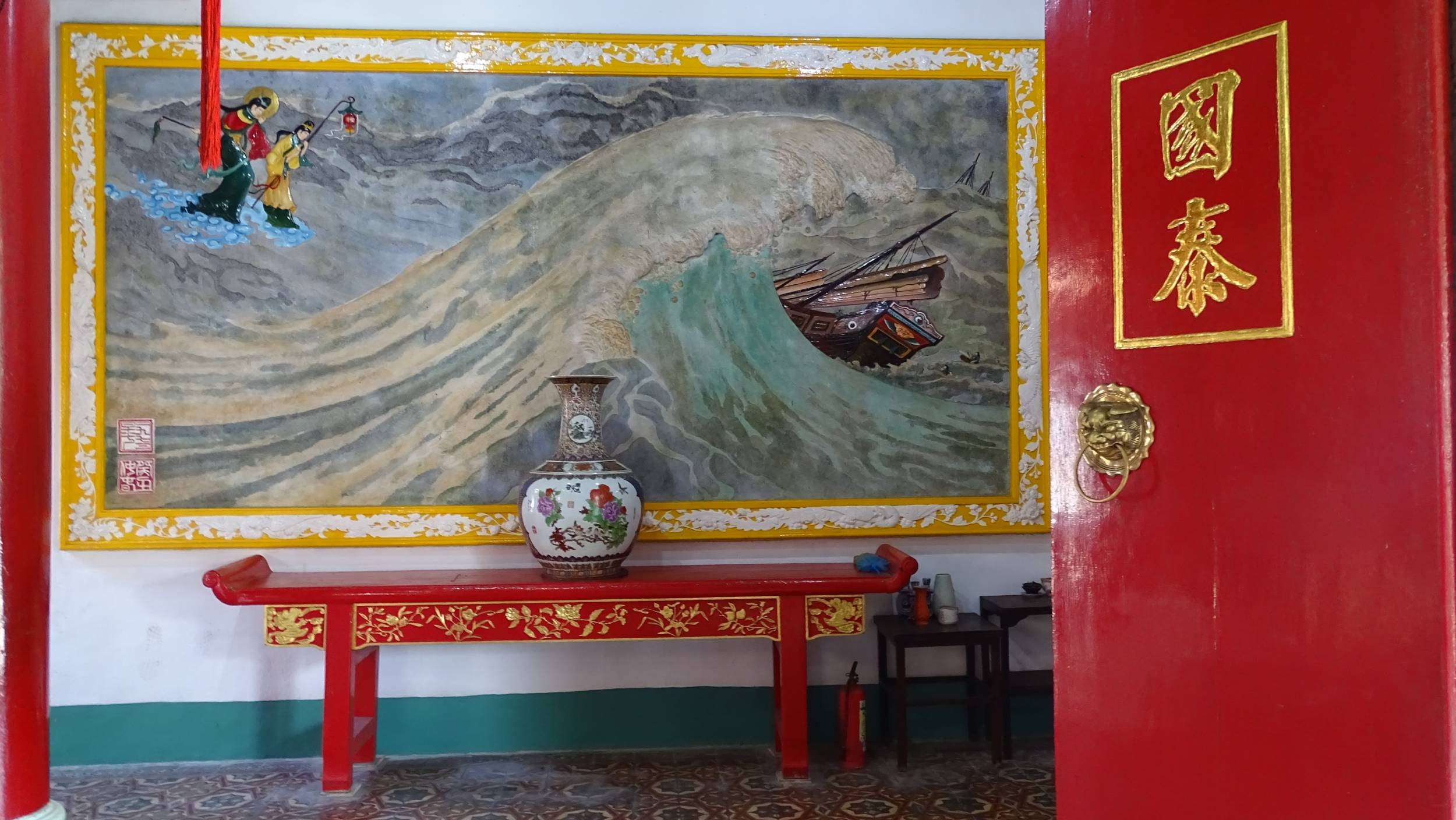 An open red door with Chinese characters, a red table with a vase and a painting with a marine scene inside Phuc Kien Assembly Hall