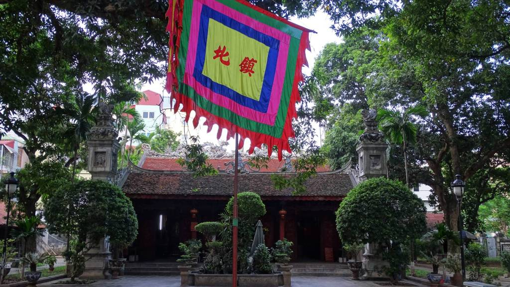 Large colourful banner set on a pole in the courtyard in front of the old Quan Thanh temple in Hanoi