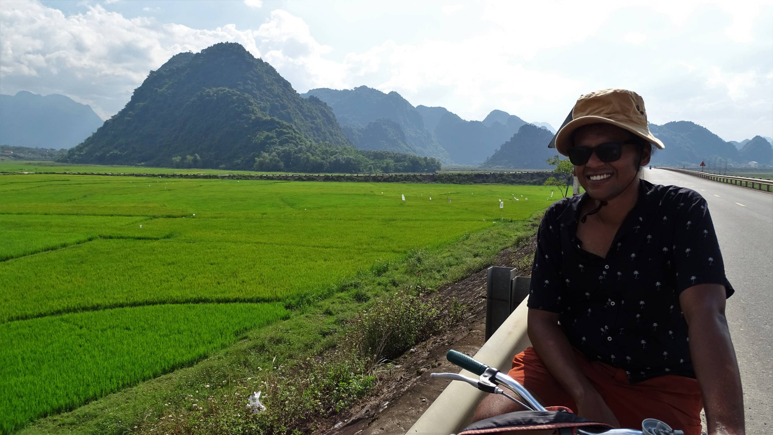 Cycling on the empty highway from Phong Nha Town with the  views of verdant green rice fields and forest-clad, mountains