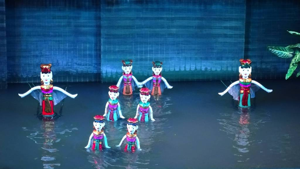 Colourful, wooden figurines of the fairies immersed in water at the Water Puppet Theatre in Hanoi