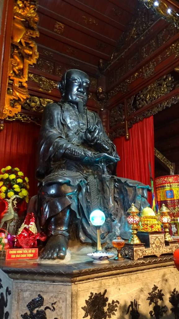 A large, bronze statue of a seated male deity at the altar in Quan Thanh temple in Hanoi