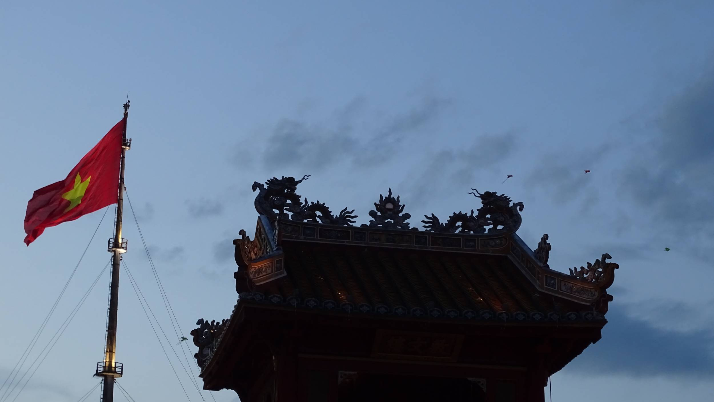 A flagpole with a Vietnamese flat, an oriental tower decorated with dragons and kites against the backdrop of the evening sky