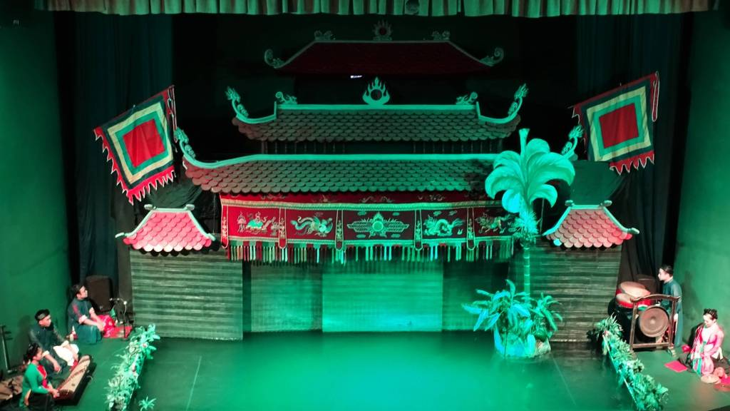 The stage of the Vietnamese Water Puppet theatre shaped as an oriental palace illuminated in green and with the small stage for musicians on the sides