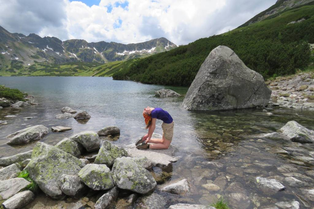 Doing a camel yoga pose on a rock at the lake in Polish Tatras