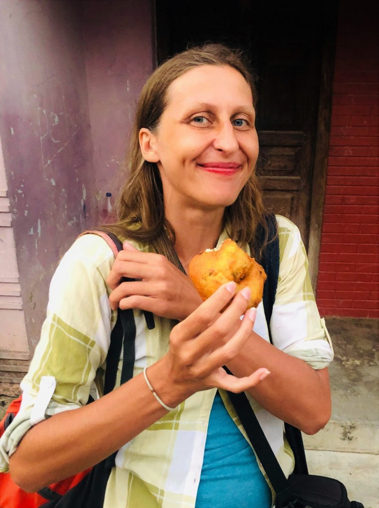 The smiling author standing on the street, holding a deep fried Sri Lankan doughut called vada in her hand.