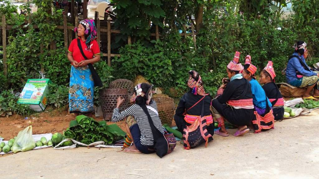 Akha Puli women  in the characteristic, tall red hats  squatting in front of the products to sell on a market in Laos