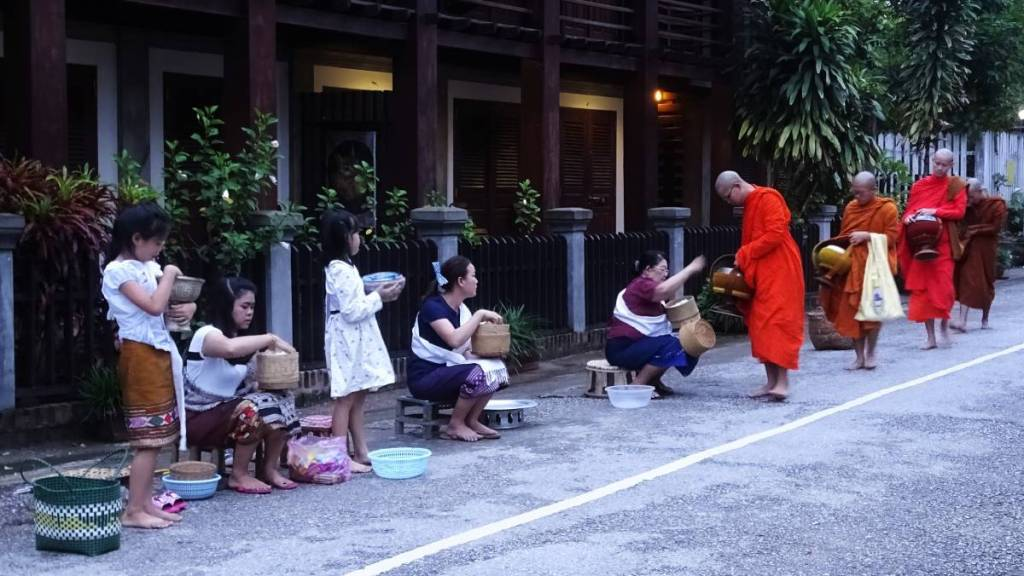 Laotian women sitting in a row on the street, waiting with the bamboo baskets full of sticky rice to share it with a line of monks in orange robes carrying large bowls for alms
