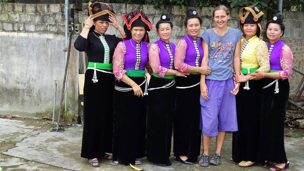 Posing with the whole group of Tai ladies in their traditional outfits: long black skirts and blouses and typical hairstyle: a bun on top of the head decorated with a single coin