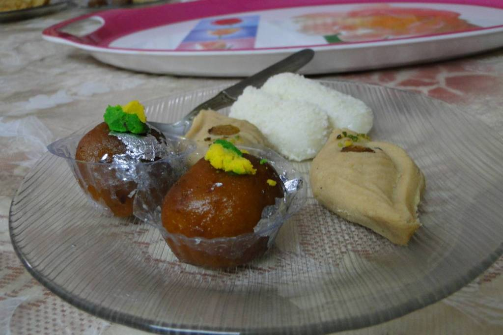 A plate with Bengali sweets: conch-shaped, cylinder-shaped and round shaped soft, milky sweets