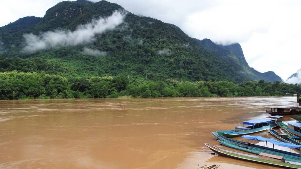 Narrow laotian boats moored at the bank of swelled, brown rive face the cloud covered green mountains on the other bank.