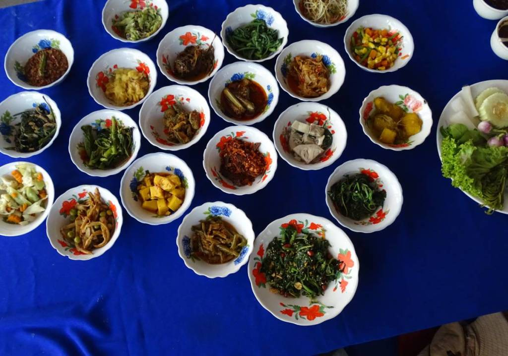 21 little bowls full of different vegan dishes with accompanying salad and sauces