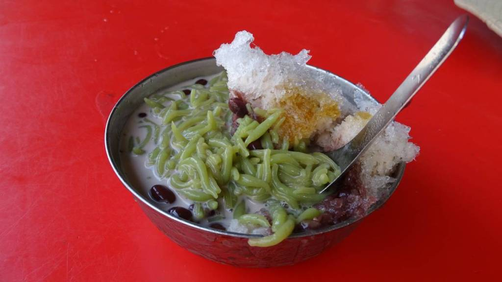 A metal bowl with cendol- Malaysian dessert made of green rice-flour jelly, red beans and crushed  ice