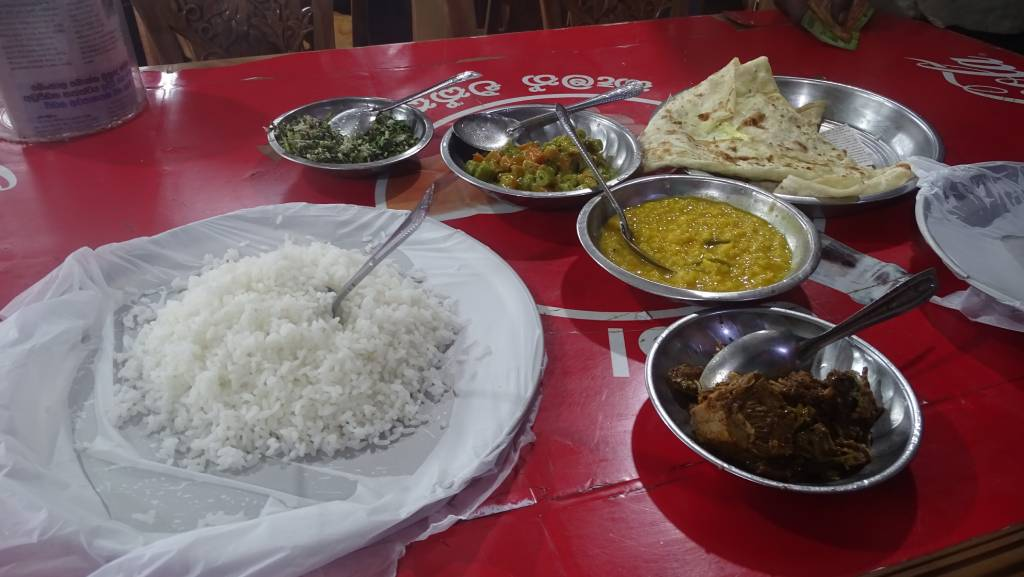 A plastic table full of steel plates and bowls, some covered with sheets of polyethylene , containing vegetarian dishes, rice and flat bread. A cheap eatery in Haputale, Sri Lanka.