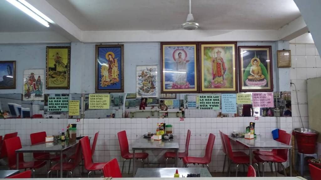 The interior of com chai- Vietnamese vegan eatery catering for devout Buddhist with plastic chair and tables and framed religious pictures on the walls.