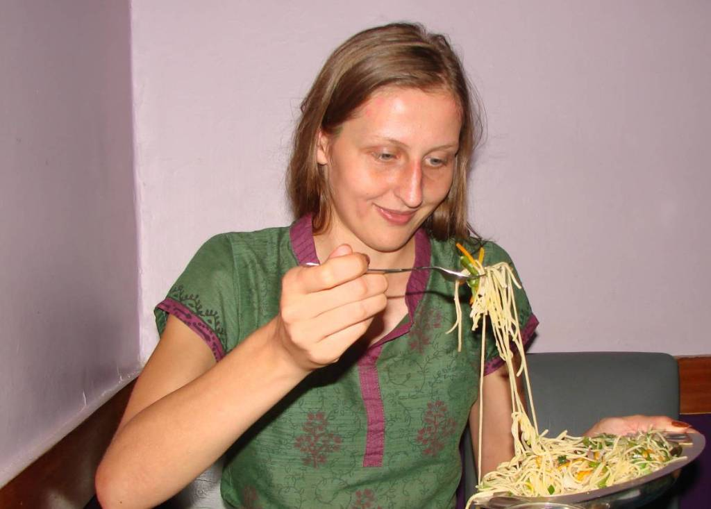 The author hoding in her hand a fork full of chow- Indian style vegetarian noodles