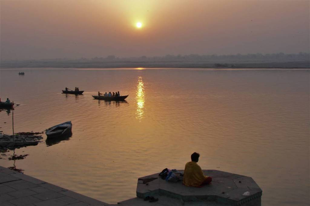 A ghat in Varanasi at sunrise. A view from above at the boats on Ganges and a man meditating at the stone platform.
